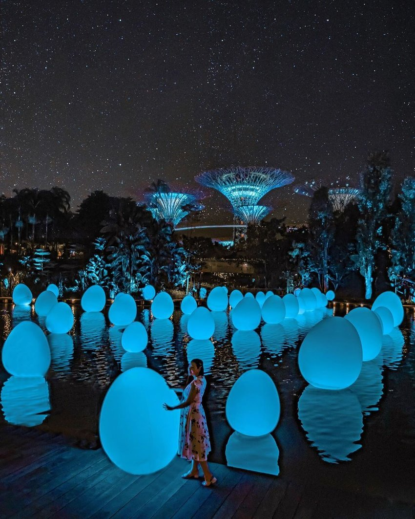 A girl standing by a lake filled with egg-shaped lights installation