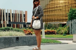 At the new City of Dreams in Manila, wearing a basic black dress with clean white accessories: bucket bag and mandals.