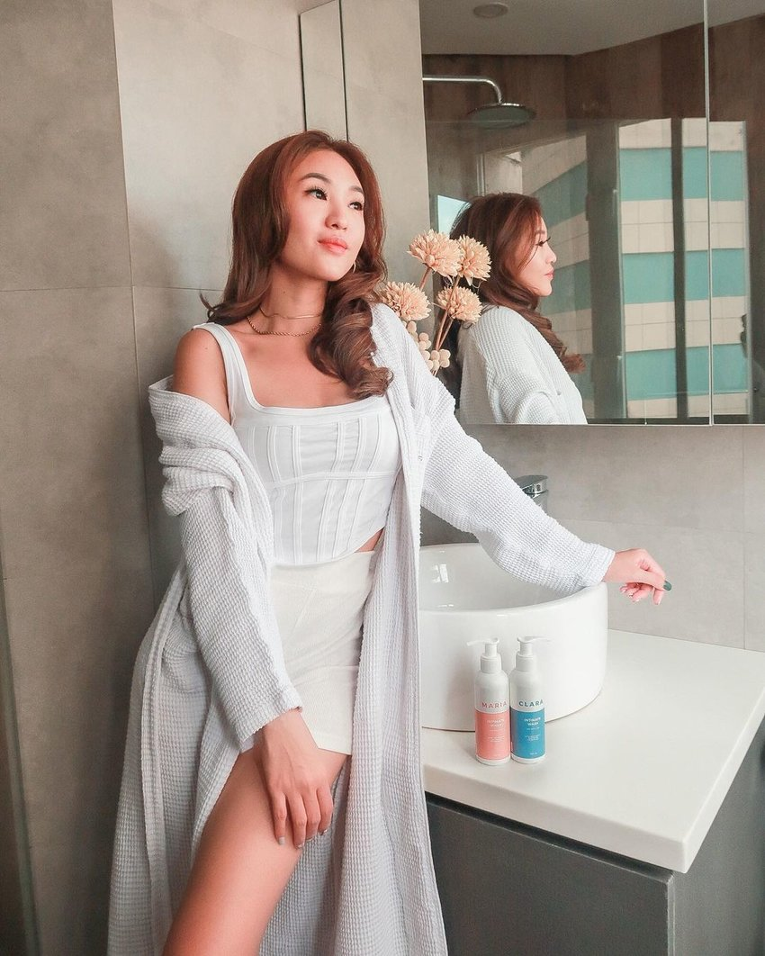 woman in soft white outfit by bathroom