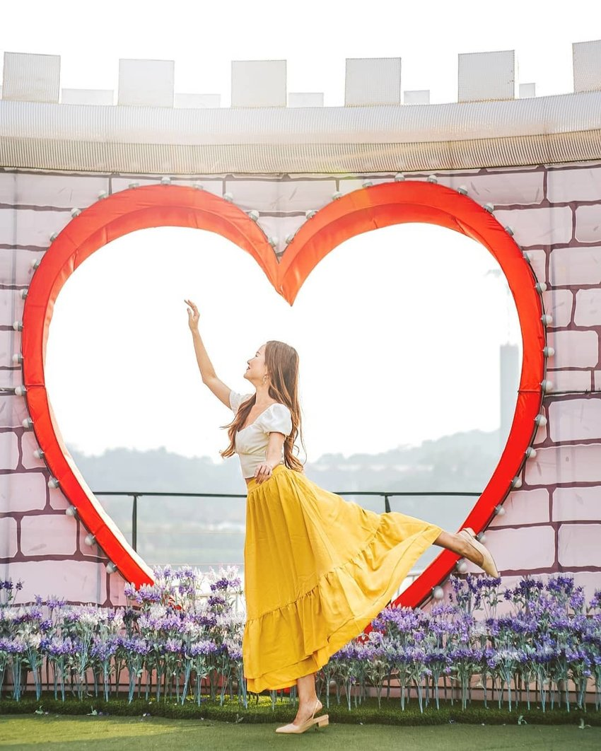 A woman posing at a photo spot with a heart shape background and a nice view