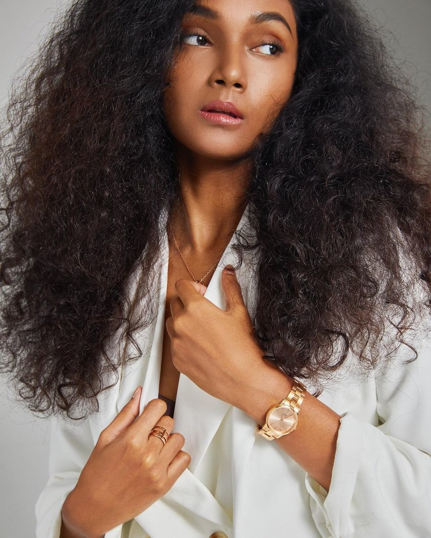 woman with curly hair and gold accessories