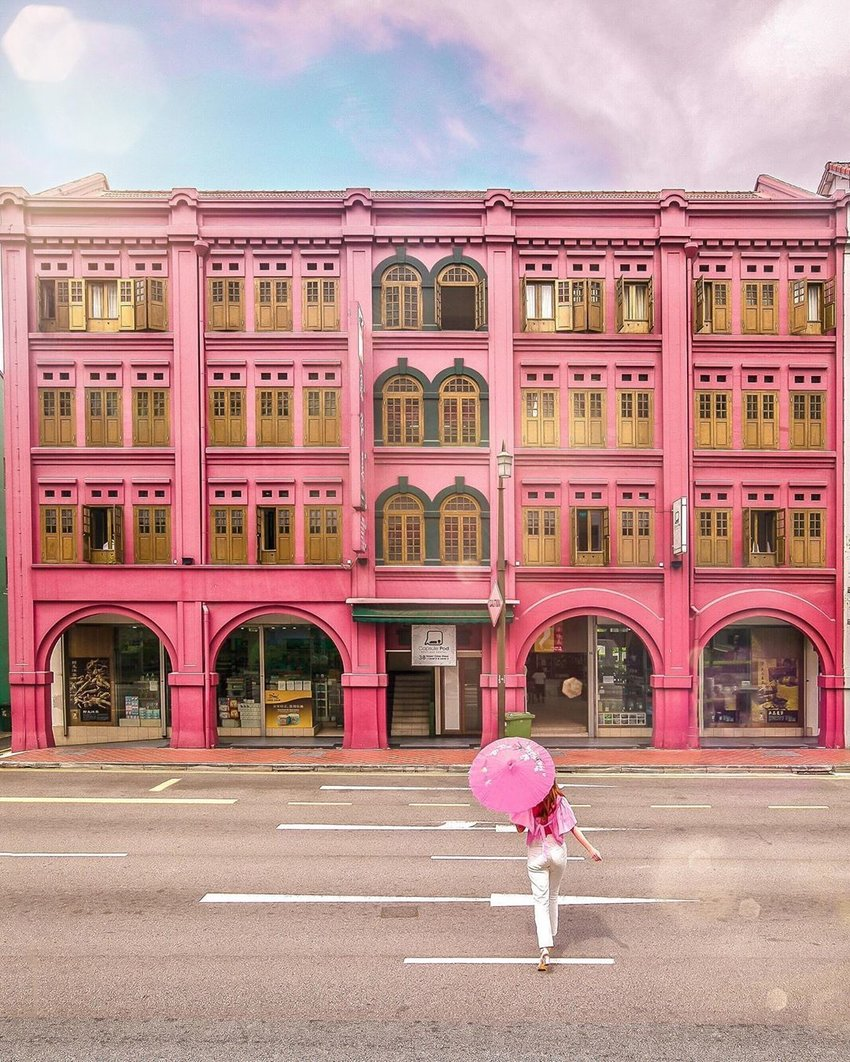 Girl crossing the street towards a pink building