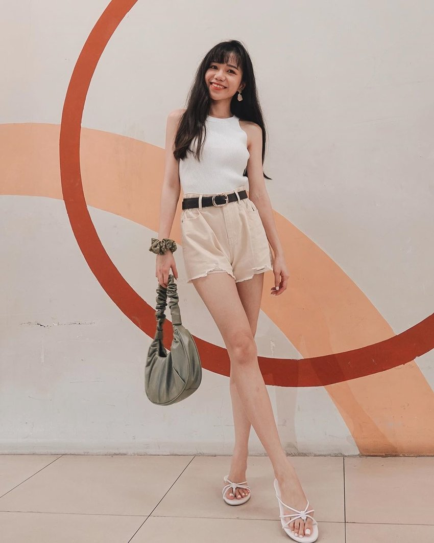 Girl wearing white top and neutral shorts