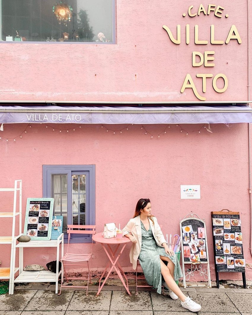 A girl sitting in front of a pink cafe